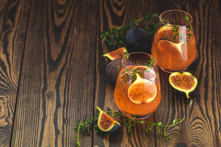 Pink cocktail with fig, thyme and ice in glass on dark wooden background, close up. Summer drinks and alcoholic cocktails. Alcoholic or detox cocktail 写真素材 - 132823536