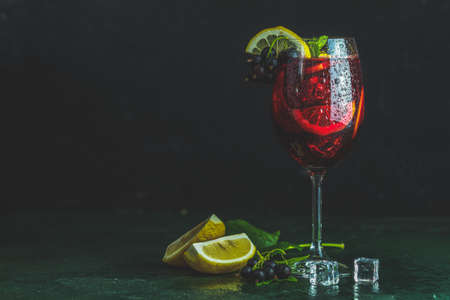 Cold red cocktail with blackcurrant, lemon, mint and ice in tall glass on black background. Summer drinks and alcoholic cocktails. Alcoholic cocktail Blackcurrant mojito