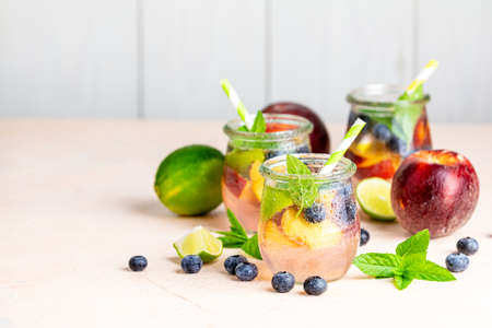 Blueberry and peach infused water, cocktail, lemonade or tea in jar with water drops. Summer iced cold drink with blueberry, lime, peach and mint 写真素材