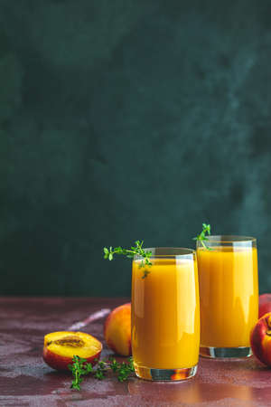 Glass of fresh healthy peach smoothie or juice on dark concrete surface table. Shallow depth of the field, close up, copy space for you text