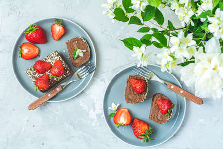 Chocolate rollcake with fresh strawberries on ceramic plate, jasmine and white peonies on light gray concrete surface table. Top view, flat lay, copy space for you text 写真素材