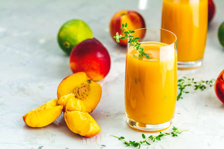 Glass of fresh healthy peach smoothie or juice on light gray concrete surface table. Shallow depth of the field, close up, copy space for you text