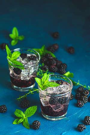 Cold summer berry drink with blackberries. Refreshing summer drink with syrup, blackberry and ice on dark blue concrete background