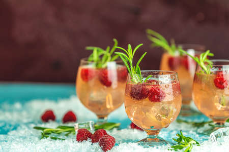 Fresh raspberry cocktail with rosemary and ice in glasses with water drops on dark background. Christmas and New Year holiday welcome drink. 写真素材 - 132823594