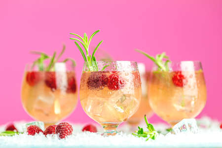 Fresh raspberry cocktail with rosemary and ice in glasses with water drops on pink background. Christmas and New Year holiday welcome drink.