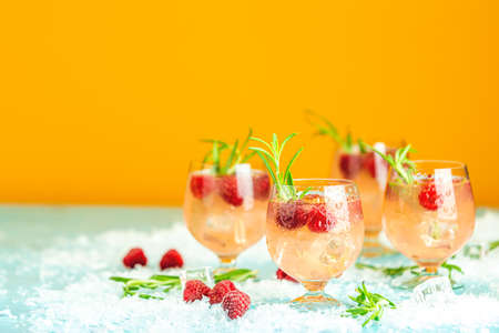 Fresh raspberry cocktail with rosemary and ice in glasses with water drops on yellow background. Christmas and New Year holiday welcome drink.