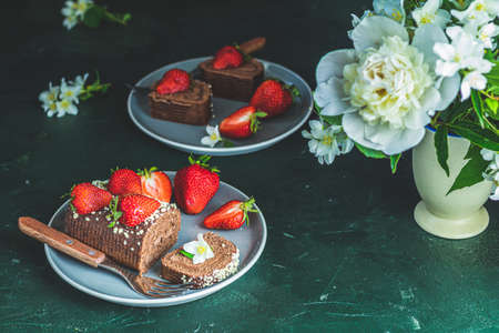 Chocolate rollcake with fresh strawberries in ceramic plate, jasmine and white peonies on dark green concrete surface table