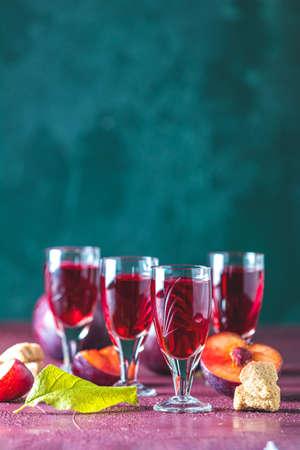 Pflaumen starkes alkoholisches Getränk in Schüssen. Schnaps, Slivovica, Pflaumenbrand oder Pflaumenwodka mit reifen Pflaumen auf dunkelgrüner und bordeauxroter Betonoberfläche.