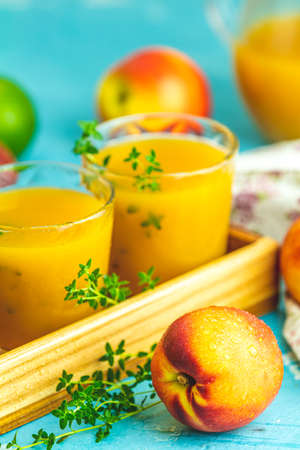 Glass of fresh healthy peach smoothie or juice in wooden box on light blue concrete surface table. Shallow depth of the field, close up, copy space for you text.