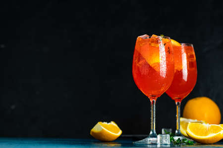 Two Aperol spritz cocktail in big wine glass with oranges, summer Italian fresh alcohol cold drink. Dark bar counter background with tools, summer mood concept, selective focus 写真素材 - 133181433