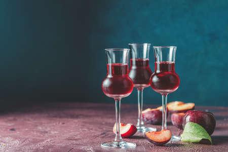 Pflaumen starkes alkoholisches Getränk in Grappas Weinglas mit Tau. Schnaps, Slivovica, Pflaumenbrand oder Pflaumenwodka mit reifen Pflaumen auf dunkelblauer und bordeauxroter Betonoberfläche.