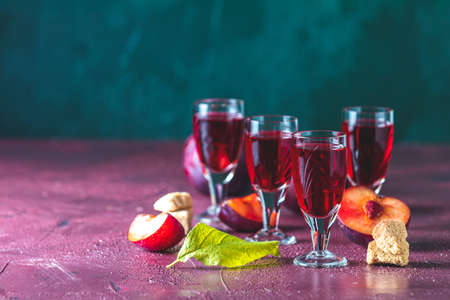 Plums strong alcoholic drink in shots. Hard liquor, slivovica, plum brandy or plum vodka with ripe plums on dark green and  claret bordeaux concrete surface.