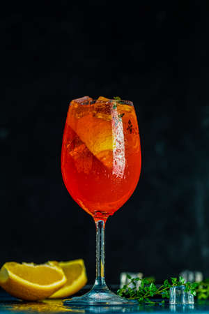 Cocktail aperol spritz in big wine glass with water drops on dark background. Summer alcohol cocktail with orange slices. Italian cocktail aperol spritz on slate board. Trendy beverage.