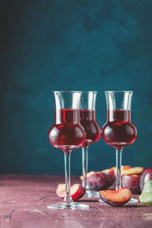 Pflaumen starkes alkoholisches Getränk in Grappas Weinglas mit Tau. Schnaps, Slivovica, Pflaumenbrand oder Pflaumenwodka mit reifen Pflaumen auf dunkelblauer und bordeauxroter Betonoberfläche. Standard-Bild