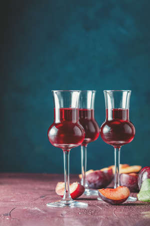 Plums strong alcoholic drink in grappas wineglass with dew. Hard liquor, slivovica, plum brandy or plum vodka with ripe plums on dark blue and  claret bordeaux concrete surface. 写真素材 - 133190598