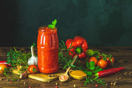 Homemade DIY natural canned hot tomato sauce chutney with chilli or adjika in glass jar standing on wooden table with cherry tomatoes, salt, pepper,  herbs, selective focus 写真素材