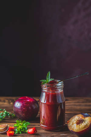 Homemade DIY natural canned hot plum sauce chutney with chilli or tkemali in glass jar standing on wooden table with ingredients : plum, salt, pepper,  herbs, selective focus
