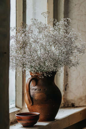 Beautiful retro still life with wild flowers in clay jug on windowsill of an old window. Close up, shallow depth of the field, copy space for text. 写真素材