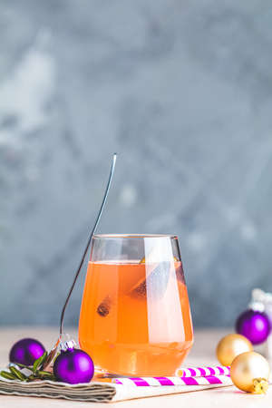 Christmas and New Year pink cocktail with fig and cinnamon  in glass on pink concrete background, close up, surrounded  holiday decor. Winter festive drinks and alcoholic cocktails or detox drink 写真素材