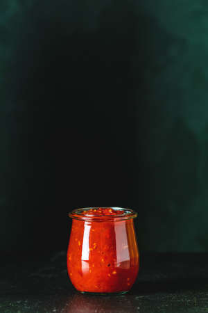 Homemade DIY natural canned hot tomato sauce chutney with chilli or adjika in glass jar standing on wooden table, selective focus, copy space for text