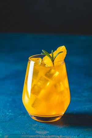Yellow orange cocktail with tangerine and rosemary in glass on dark blue concrete background, close up. Christmas and New Year  holiday welcome drink. Alcoholic or detox cocktail