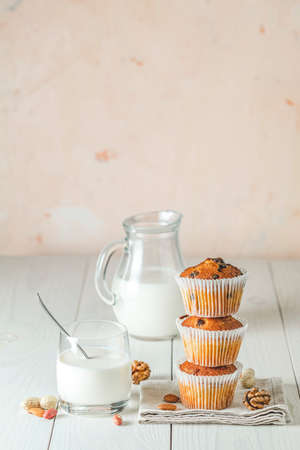 Vanilla caramel muffins in paper cups and glass of milk on white wooden background. Delicious cupcake with raisins, almonds and nuts. Homemade biscuit cakes. Copy space for text. 写真素材