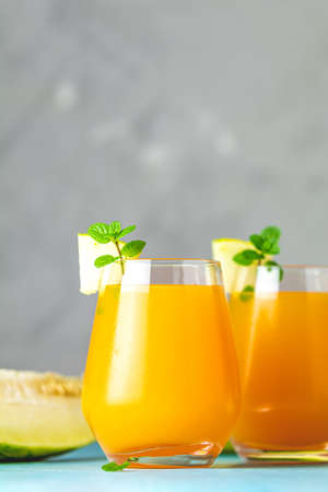 Yellow orange cocktail with melon and mint in glass on blue concrete background, close up. Summer drinks and alcoholic cocktails. Alcoholic or detox cocktail 写真素材