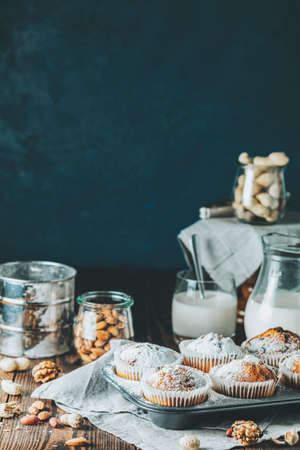 Vanilla caramel muffins in paper cups and glass in bakeware of milk on  dark wooden background. Delicious cupcake with raisins, almonds and nuts. Homemade biscuit cakes. Copy space for text. 写真素材