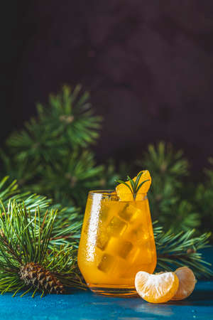 Yellow orange cocktail with tangerine and rosemary in glass on dark blue concrete background decorated pine branches with cones, close up. 写真素材