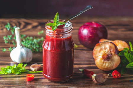 Homemade DIY natural canned hot plum sauce chutney with chilli or tkemali in glass jar standing on wooden table with ingredients — plum, salt, pepper,  herbs, selective focus 写真素材