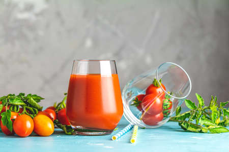 Glasses of fresh delicious jummy red tomato juice and fresh raw tomatoes with pink salt in spoon on light concrete surface. Close up. Gmo free. Natural good food. 写真素材