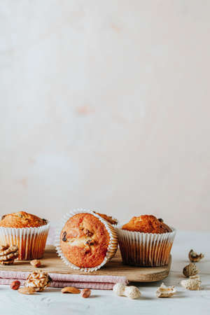 Vanilla caramel muffins in paper cups on white wooden background. Delicious cupcake with raisins, almonds and nuts. Homemade biscuit cakes. Copy space for text. 写真素材