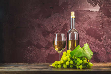 Glasses and bottles of wine and grapes on dark claret bordeaux concrete surface background