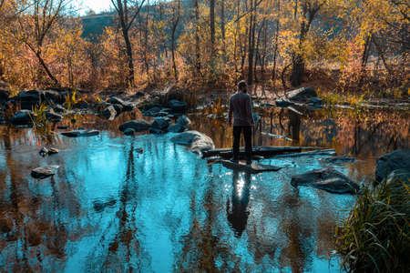 Young man runs over a river on a rock. Amazing reflection trees and sunny light in water. Terrific view of the River Canyon on sunny cloudy fall day. Beautiful autumn river landscape. 写真素材