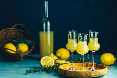Limoncello with thyme in three grappas wineglass in wooden tray, fresh lemon in basket. Artistic still life on dark blue background 写真素材