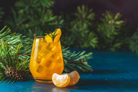 Yellow orange cocktail with tangerine and rosemary in glass on dark blue concrete background decorated pine branches with cones, close up. Christmas and New Year  holiday welcome drink