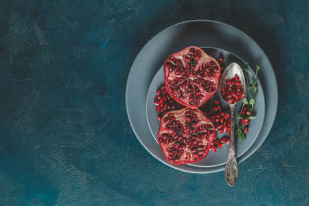 Fresh juicy pomegranate - whole and cut on a dark blue vintage background, top view, horizontal, with copy space 写真素材