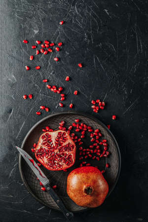 Fresh juicy pomegranate - whole and cut on a black vintage background, top view, horizontal, with copy space