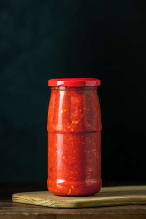 Homemade DIY natural canned hot tomato sauce chutney with chilli or adjika in glass jar standing on wooden table, selective focus 写真素材