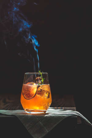 Pink cocktail with fig, thyme and ice in glass with smoke on dark wooden background, close up. Sunny light. Summer drinks and alcoholic cocktails. Alcoholic or detox cocktail