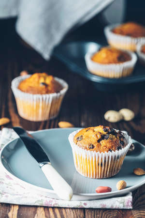 Vanilla caramel muffins in paper cups and bottles of milk on dark wooden background. Delicious cupcake with raisins, almonds and nuts. Homemade biscuit cakes. Copy space for text. 写真素材