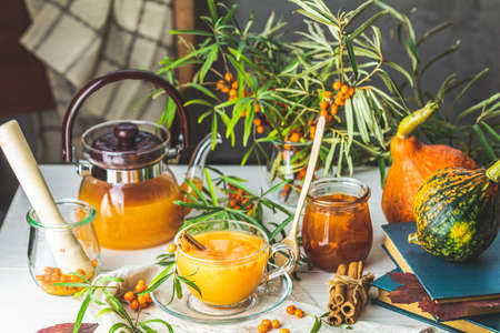 Cup and teapot of hot spicy tea with sea buckthorn, jam in the glass jar, branches of fresh berries on light woden table surface in the rustic room 写真素材