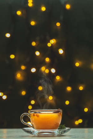 Cup of hot spicy tea with yellow orange barries on dark Christmas and New Year background with light bokeh. Beautiful holiday drink consept with copy space