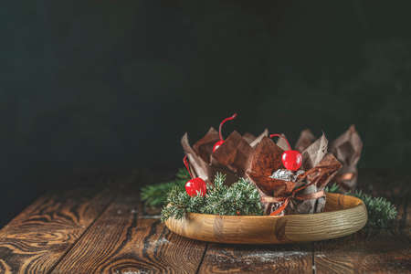 Sweet chocolate muffins decorated cherry in brown paper with ribbon on wooden bowl surrounded  pine branches. Close up, shallow depth of the field, greeting food composition.
