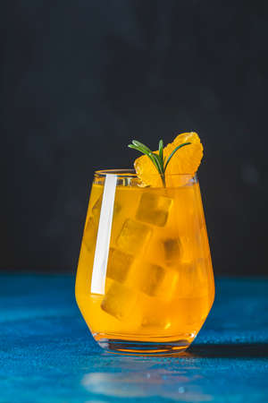 Yellow orange cocktail with tangerine and rosemary with ice in glass on dark blue concrete background , close up. Christmas and New Year holiday welcome drink 写真素材