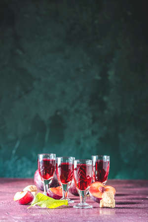 Plums strong alcoholic drink in vintage shots. Hard liquor, slivovica, plum brandy or plum vodka with ripe plums