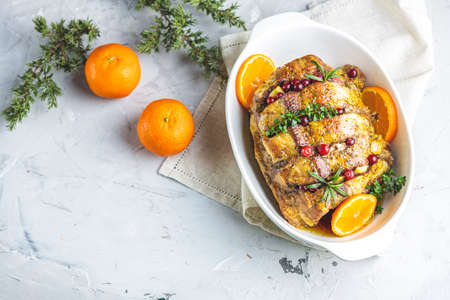 Roasted pork in white dish, christmas baked ham with cranberries, tangerines, thyme, rosemary, garlic on light table surface, close up. Stock Photo