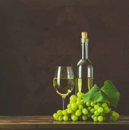 Glasses and bottles of wine and grapes on dark claret bordeaux concrete surface background.