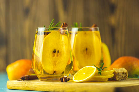 Mulled pear cider or spiced tea or grog with lemon, pear, cinnamon, anise, cardamom, rosemary. Festive summer drinks, pear spice cocktail. Hot drink cocktail for New Year, Christmas, winter or autumn holidays