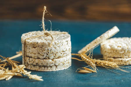 Stack of rice cakes. American puffed rice cakes. Healthy snacks with ears of wheat on classic blue concrete surface. Color of 2020 year. Classic Blue.